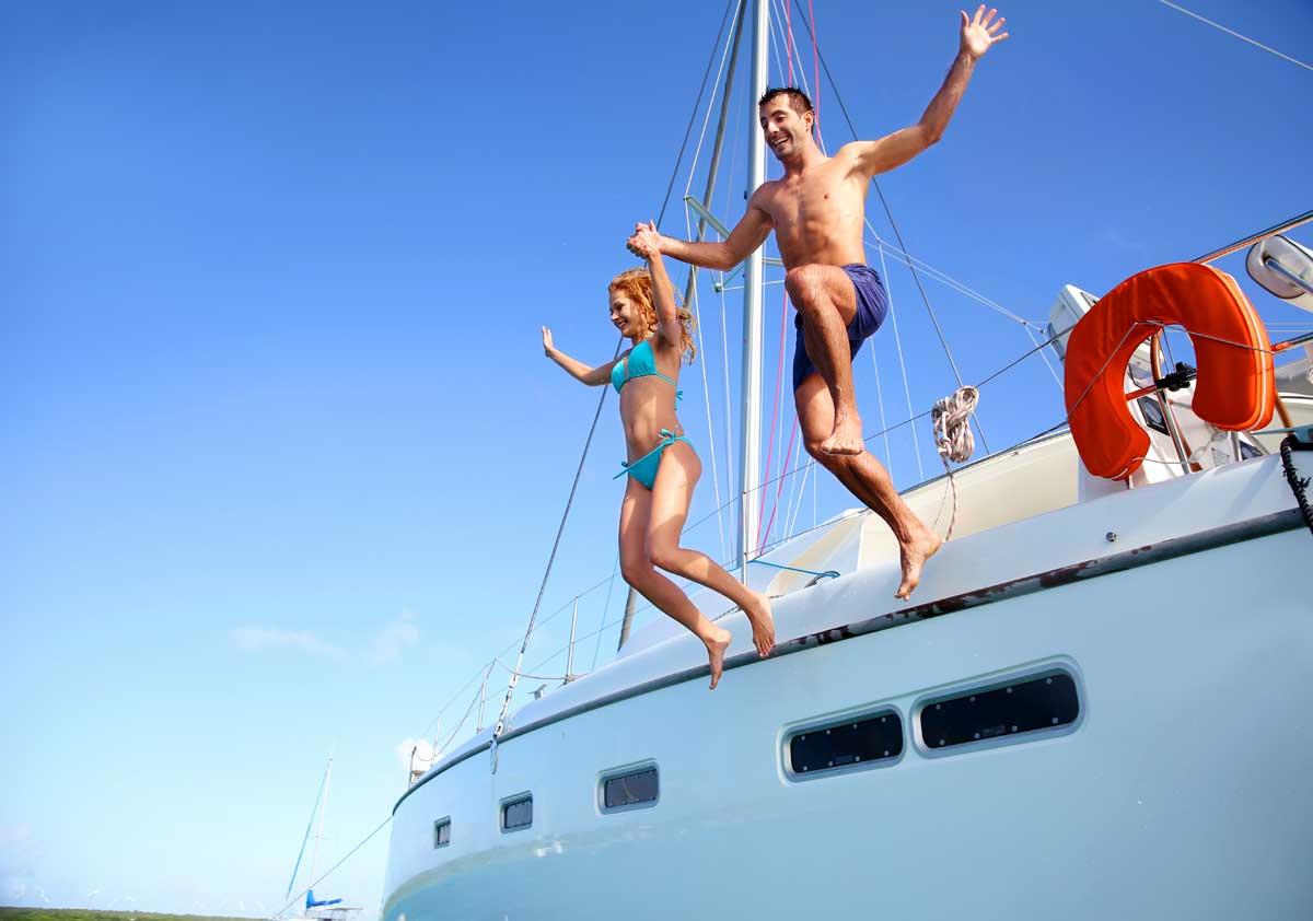 ragazzi saltando dalla barca a vela