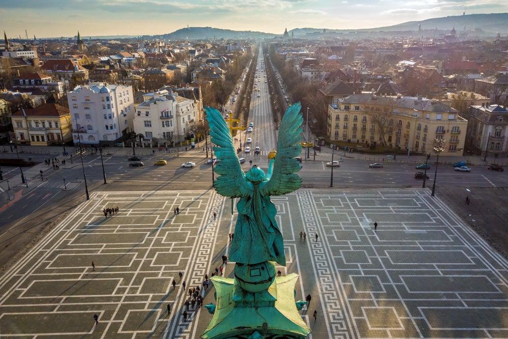 Scultura dell'angelo vista da dietro su Piazza degli eroi al tramonto con la via Andrassy e l'orizzonte di Budapest sullo sfondo