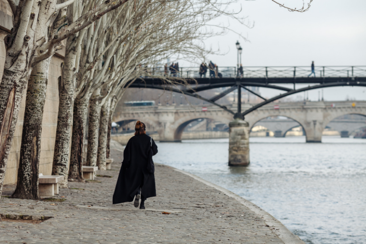 Donna in nero, passeggia lungo la Senna a Parigi