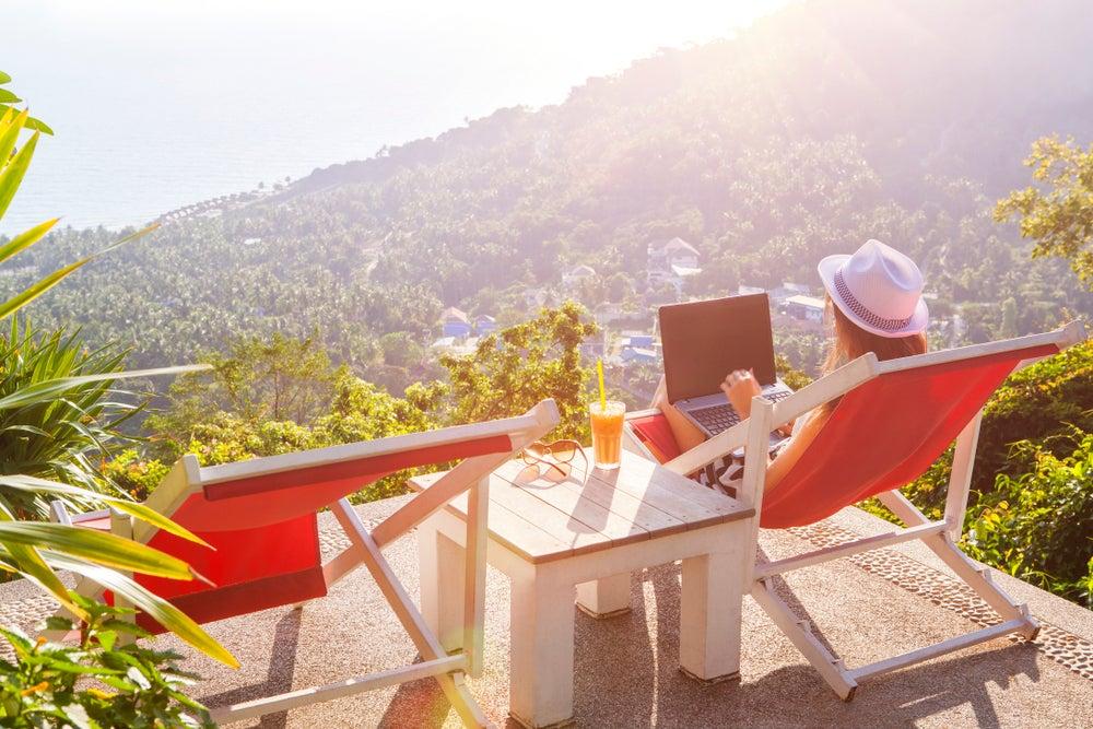 ragazza su sedia a sdraio con laptop con panorama mare