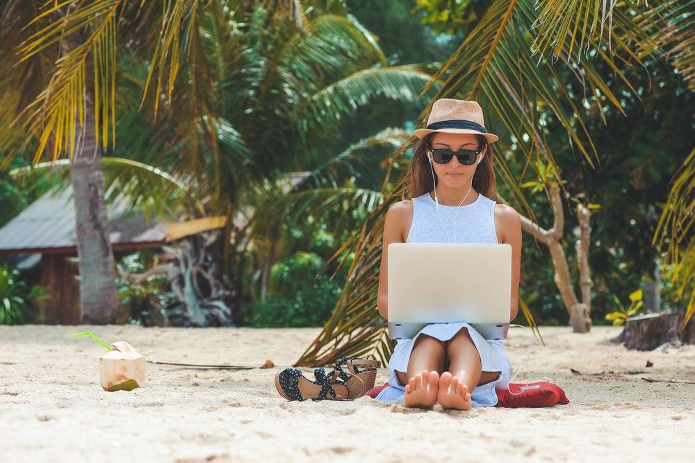 ragazza sulla spiaggia con laptop sulle ginocchia e palme sullo sfondo
